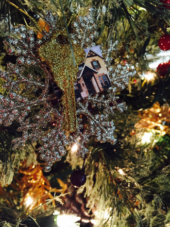 DIY glitter house key ornament hanging on tree.