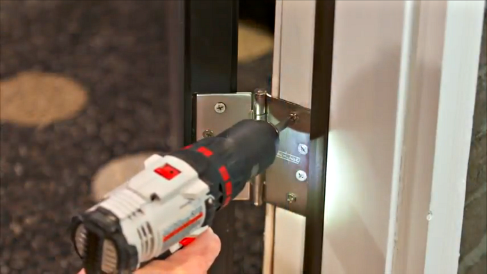 Installing door hinges with drill.
