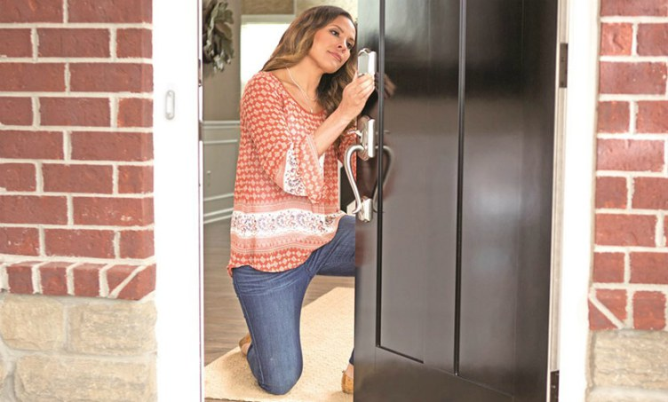 Woman installing Schlage Sense Smart Deadbolt on front door.