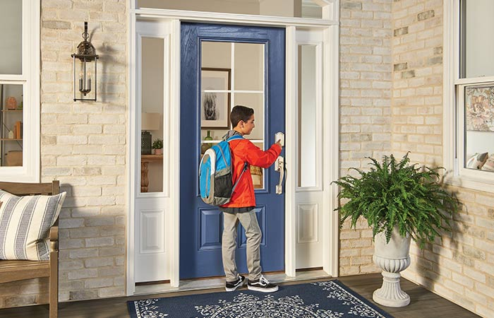 Child with backpack unlocking front door smart lock