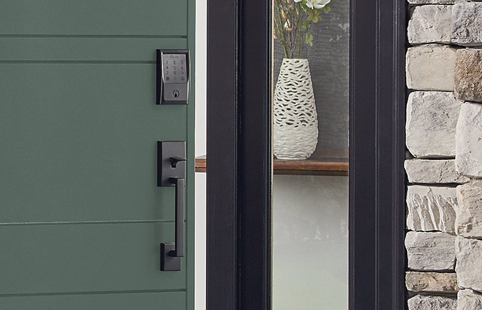 Schlage Encode Smart WiFi Deadbolt in Matte Black on green front door.
