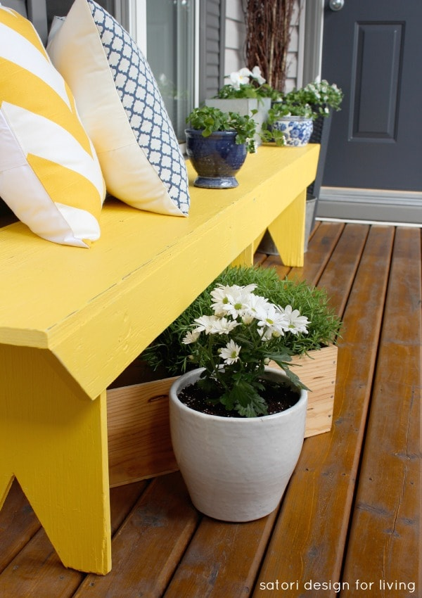 Yellow front porch bench with blue accessories.