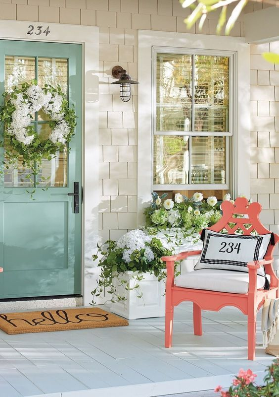 Mint blue front door with coral chair.