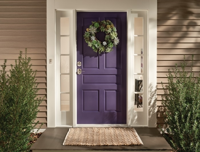 Purple front door with succulent wreath and Schlage deadbolt and keyed lever.