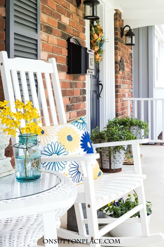 Front porch with blue and yellow flowers, pillows, door.