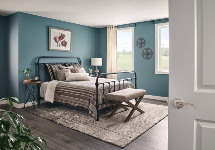 Master bedroom with teal walls, black iron frame bed and satin nickel Schlage Custom door hardware.