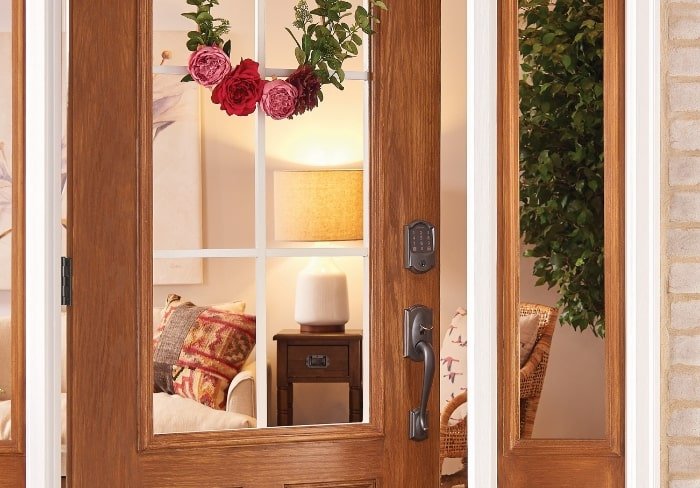 Pink floral minimal wreath on front door with Schlage smart lock.