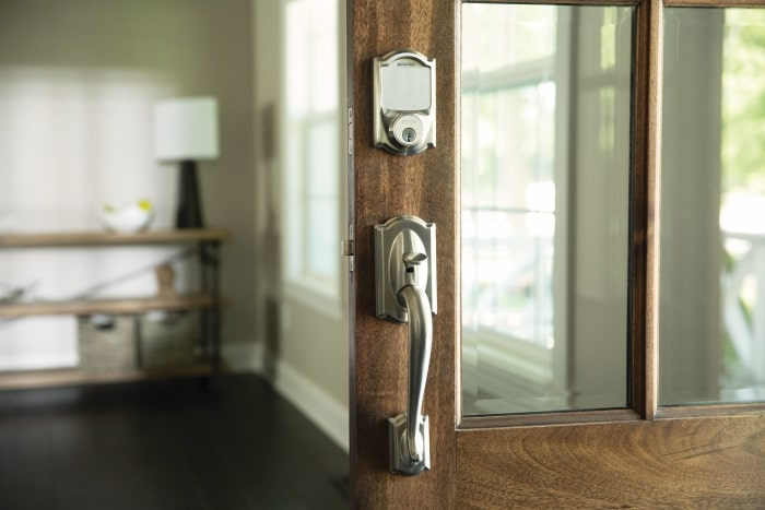 Schlage Sense Smart Deadbolt with Satin Nickel grip on glass front door.