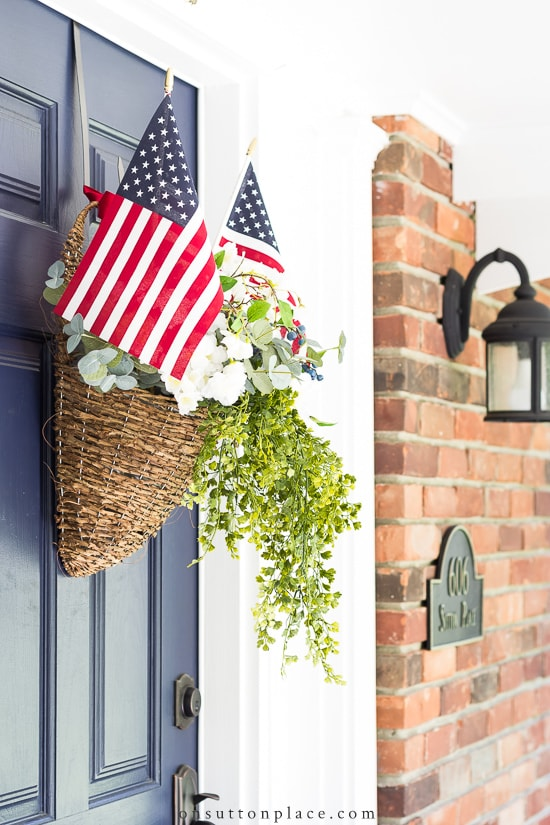 Front door hanging basket with greenery and American flags.