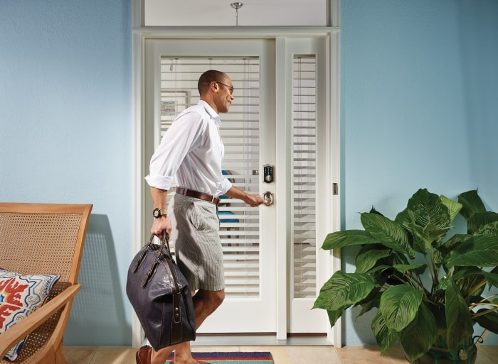 Man at front door with electronic lock.