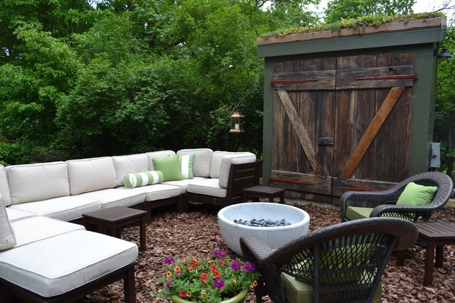Backyard patio with sectional and storage shed.
