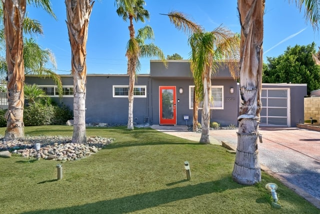 Modern vacation rental with green front door and Schlage smart lock.