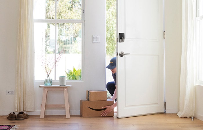 Amazon Key delivery personnel placing package inside door.