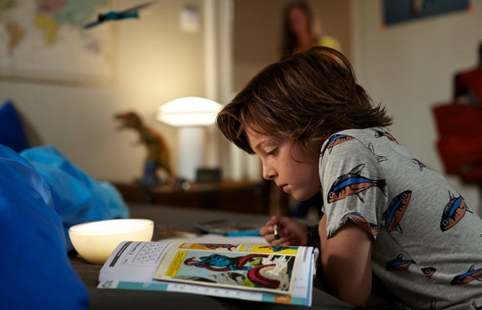 Kid reading in room with lamp on.