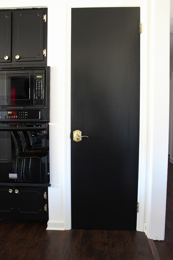 Black hollow core door with Schlage Accent lever in Satin Brass.