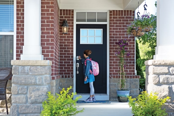 Girl with backpack unlocking Schlage Sense Smart Deadbolt.