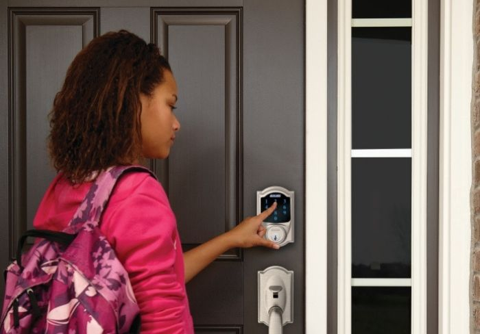 Girl with backpack unlocking Schlage Connect Smart Deadbolt.