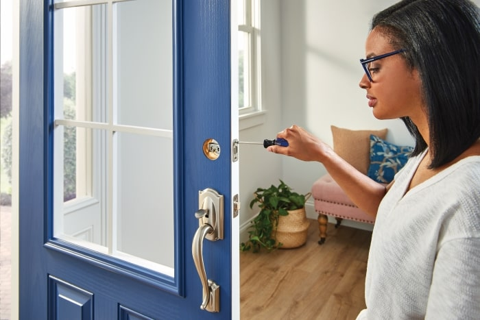 Woman installing new lock on door.