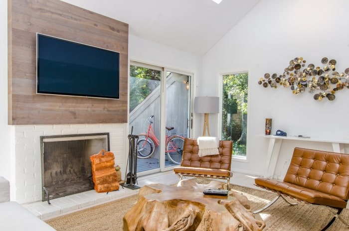 Living room with mounted tv above fireplace.