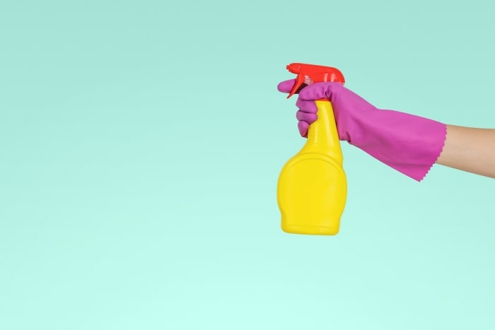 Hand with rubber glove holding household cleaner.