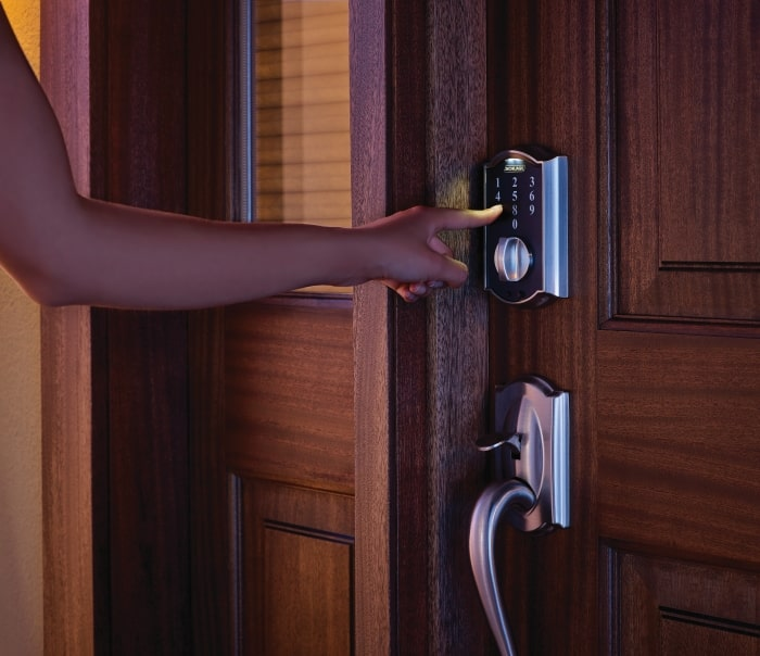 Woman entering user code on Schlage Touch Keyless Touchscreen Deadbolt.