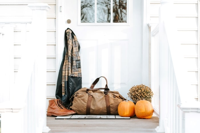 Brown duffel bag, boots and jacket on fall porch.