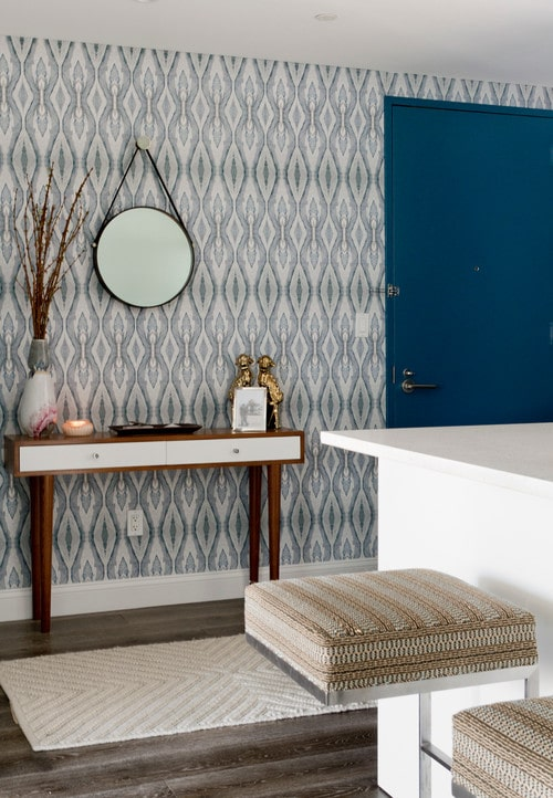 Eclectic entryway with blue printed wallpaper.