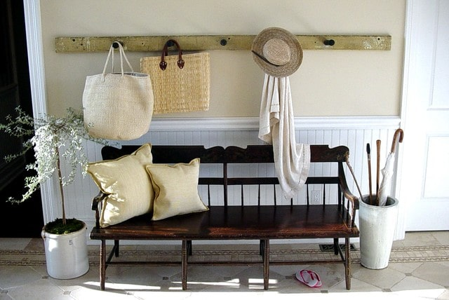 Farmhouse entryway with wall hooks and bench seating.