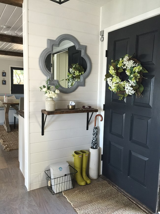 Small foyer with shelf and mirror decorated for spring.
