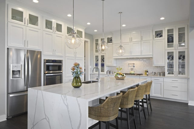 Transitional white kitchen with marble island