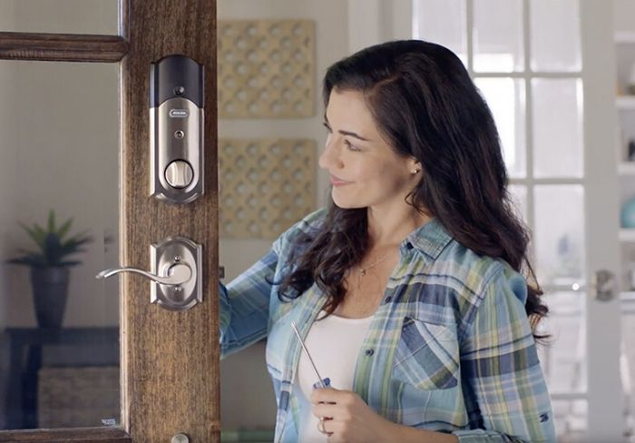 Woman installing Schlage door hardware.