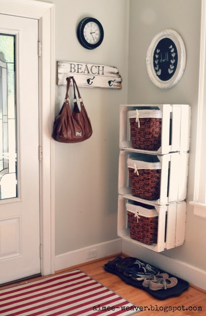 Wooden crates hung on wall for mudroom storage.