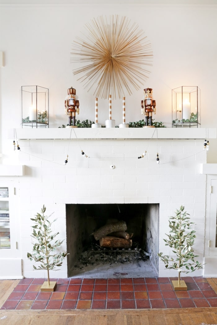 Modern holiday fireplace mantel with nutcrackers and candles.