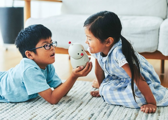 Kids holding BOCCO emo communications robot