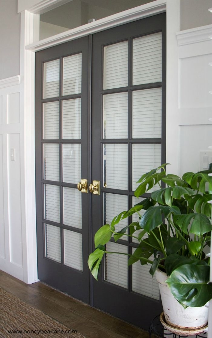 Charcoal grey French doors with Bright Brass door knobs.