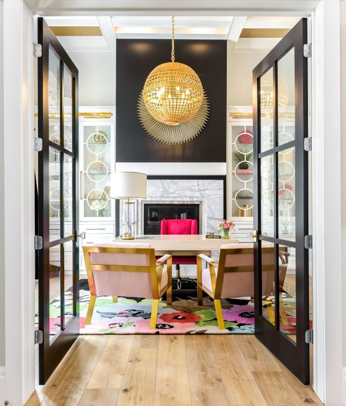 Black French doors leading into bright home office.