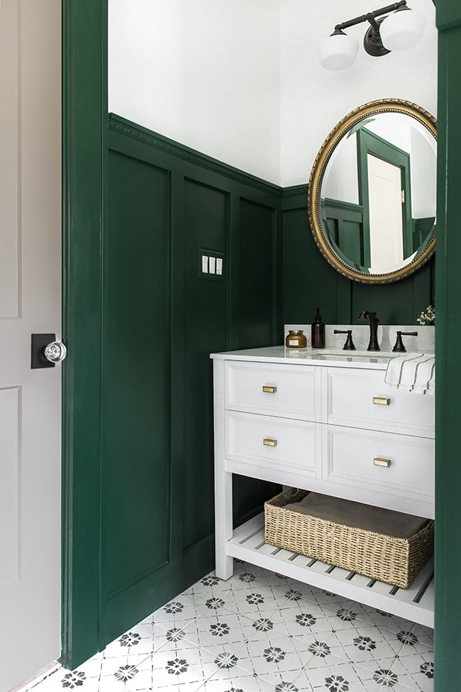 Green bathroom with black and gold finishes.