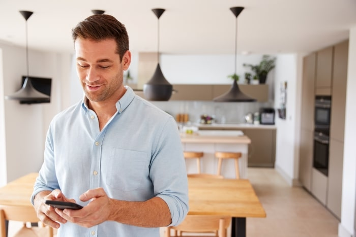 Man holding smartphone in kitchen.