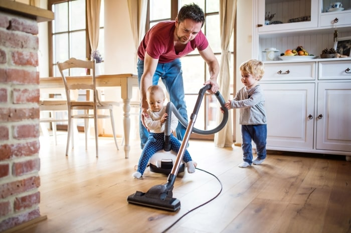 Dad vacuums kitchen with two toddlers.