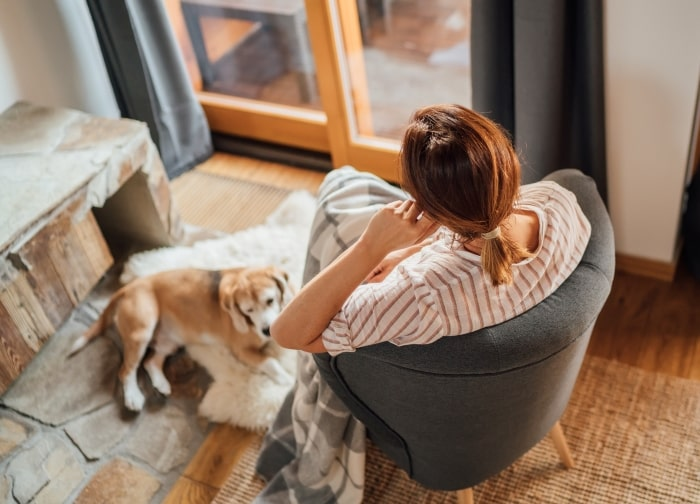 Woman sitting in chair next to dog.