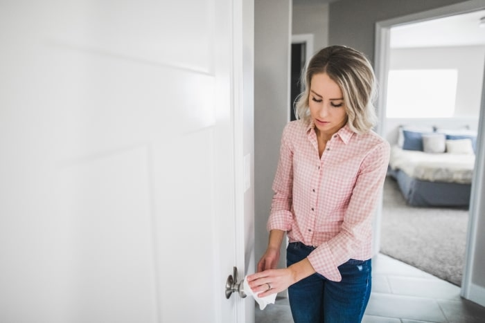 Woman cleaning door knob with cloth.