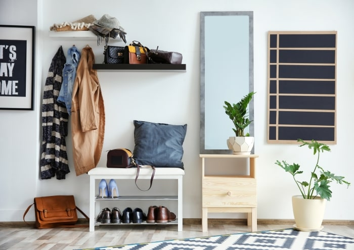 Clean entryway with coat rack and shoe storage.