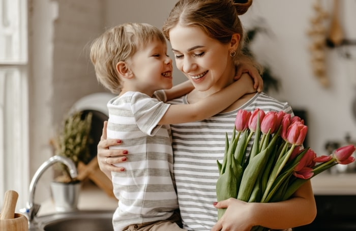 Mother hugging son while holding bouquet of tulips.