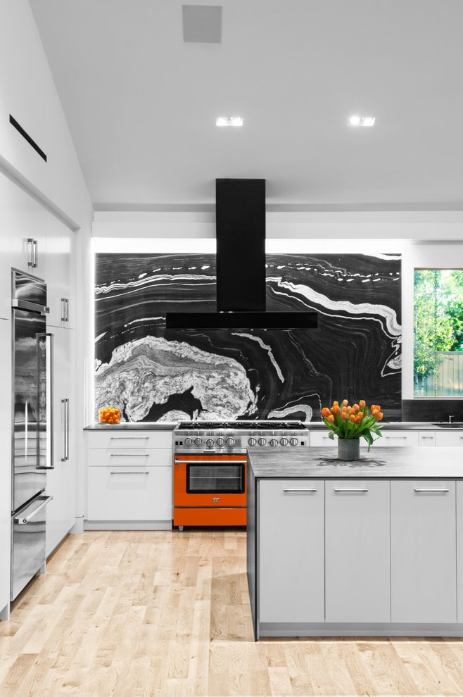 Black and white kitchen with stone slab backsplash and red oven.