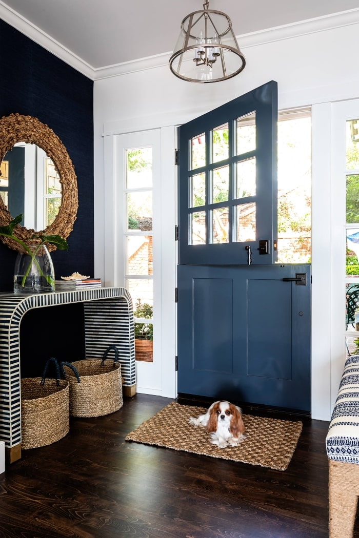 Country cottage style entryway with dark blue dutch door.