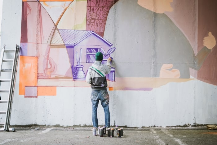 Graffiti artist painting on wall.