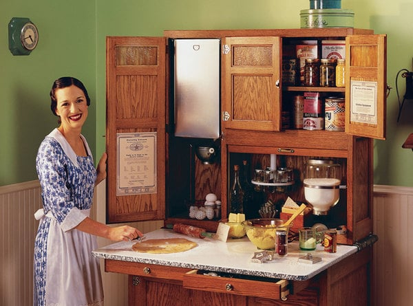 Woman standing next to Hoosier Cabinet