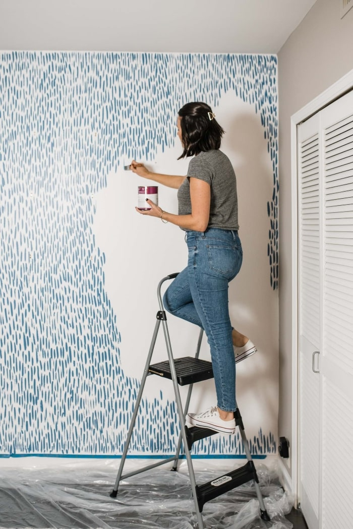 Woman using brushstrokes to paint accent wall pattern.