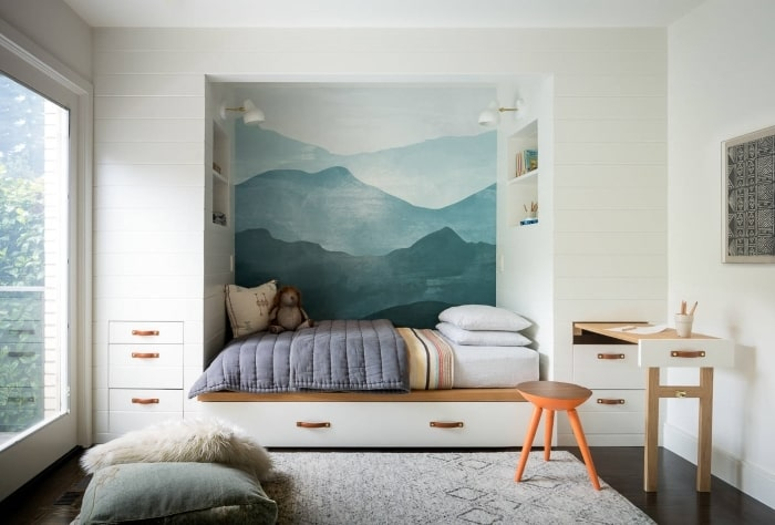 Built-in kids bed with mural of mountains painted on wall.