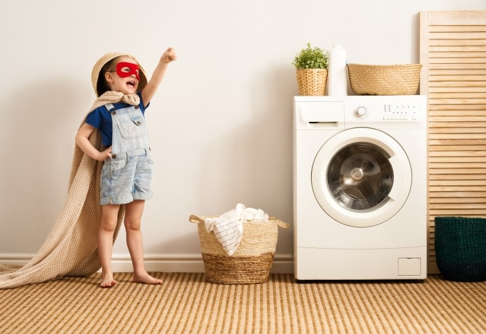 Little boy with superhero mask and blanket cape next to washing machine.